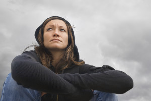 Girl sitting and contemplating on a background of a cloudy sky