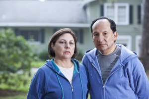 Portrait of serious senior Hispanic couple standing outside house.