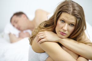 Sad woman sitting on bed and her husband sleeping in the background